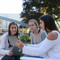 3 female students looking at their iPads together outside on campus. Merrimack College. Photograp...