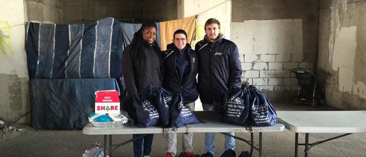Merrimack students Deidra Collins, Oscar Zepeda Cagide, and Jaime Cortes Torres help distribute needs packs on Jan. 30th, 2016.