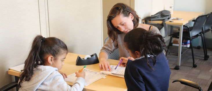 Hands to Help Graduate Fellow Hallie Dowling-Huppert tutoring two students.