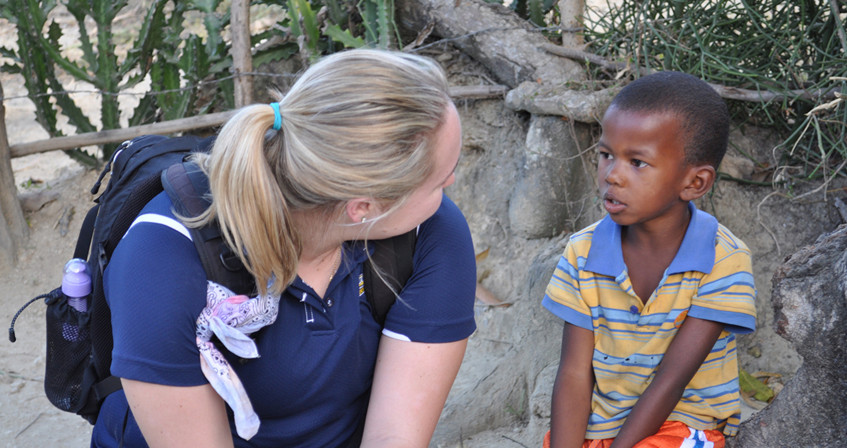 Student on service learning trip to Haiti talks with young student.