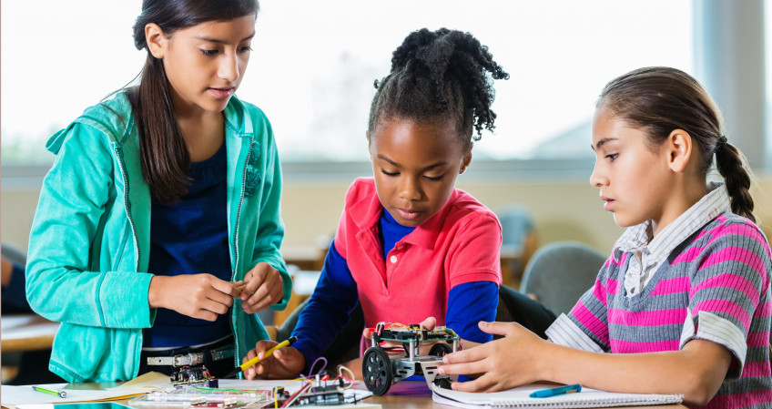 Elementary age Hispanic, African American, and Caucasian little girls are building a small robot ...