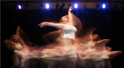 Dancer whose image is blurred by her motion on stage
