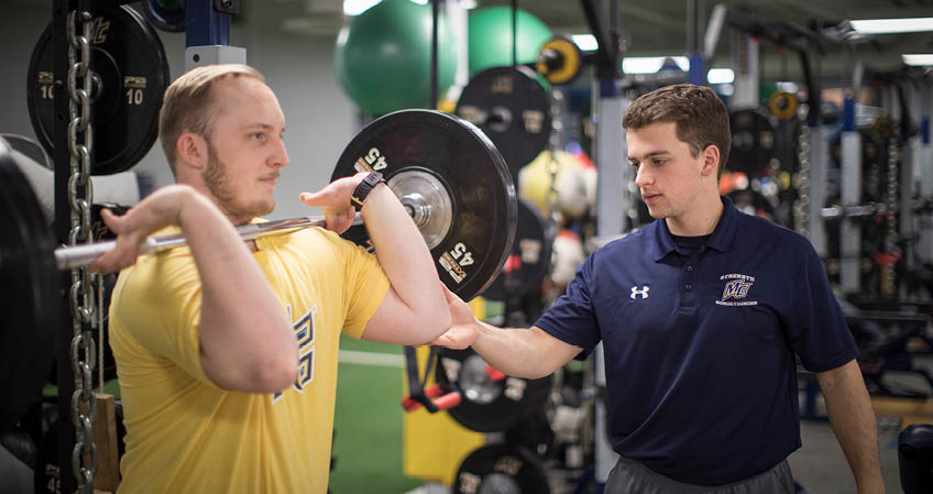 Student working with man in weight room using bar and weights