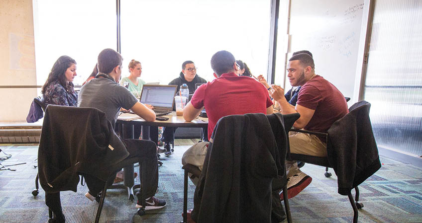 Students studying together at a round table in the library