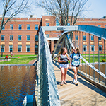 Merrimack College students walking across the bridge in the summer time