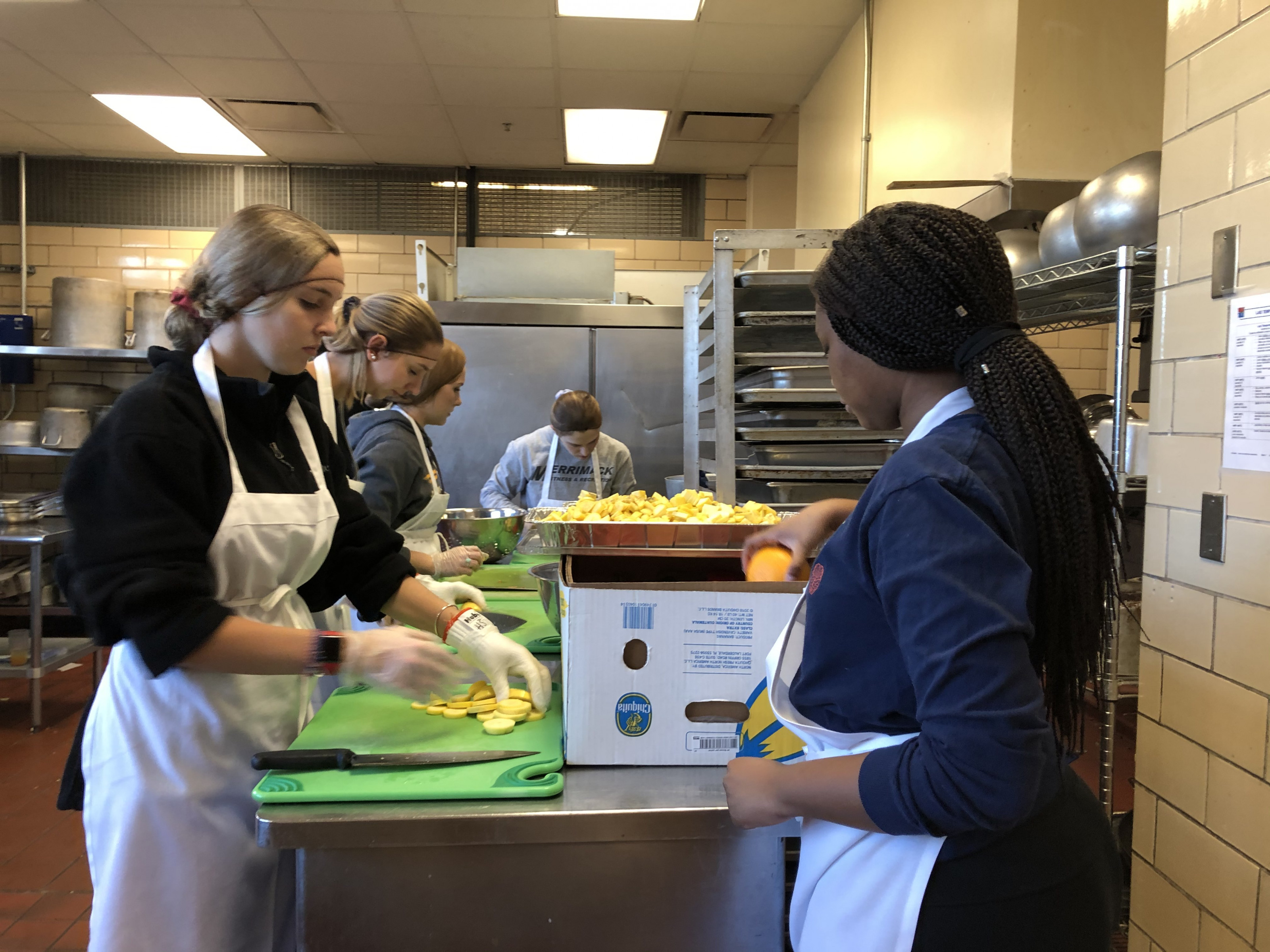 Students preparing food for Merrimack College's chapter of the Food Recovery Network.