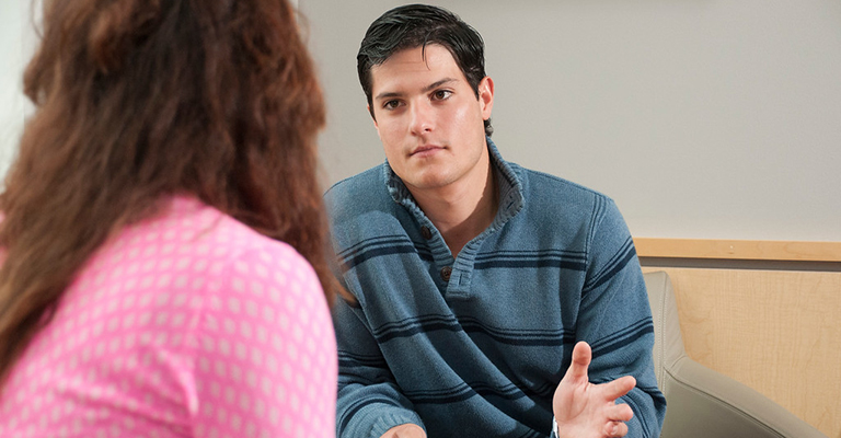 Therapist and patient talking in a counseling session.
