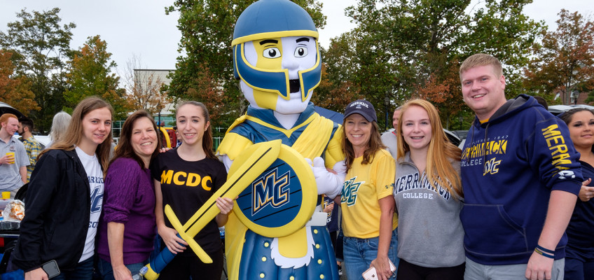 warrior mascot is flanked by merrimack supporters