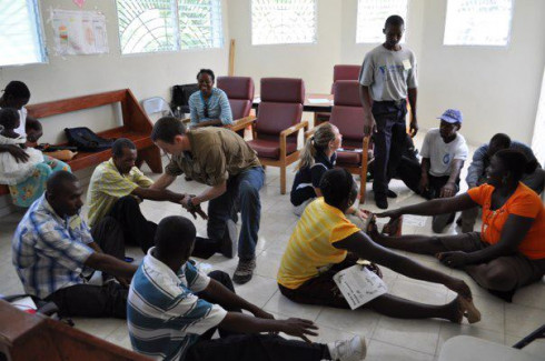 Kevin Malanson and Mollie Fitzgerald train Haitian Community Healthcare workers to use stretches to help their patients with back pain.