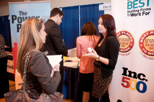 A representative from The Select Group interacts with a Merrimack College  student during the Spring 2013 Career Fair.