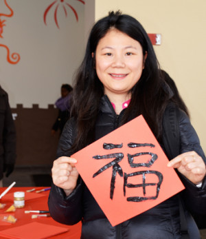 Graduate Fellow Fang Li, of Zheng Zhou, China, holds the chun lian, or good luck sign, that she made during the Lunar New Year celebration at the Sakowich Campus Center.