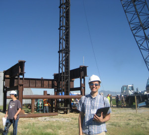 Assistant professor Jim Kaklamanos poses for a picture during the installation of the pile. The frame in the background is used to test the static axial capacity of piles after they have been driven into the ground.