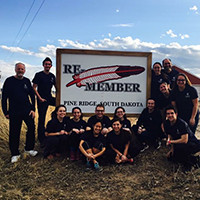Students and staff pose in front of the Pine Ridge Indian Reservation in South Dakota.