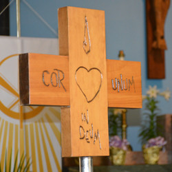 "The cross carried at all graduate commencement ceremonies bears the inscription ""cor unum in deum"" — one heart in God."""