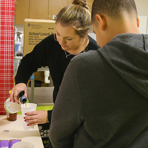 Robin pours maple syrup into a cup to dip a protein bar in as students select nutritious shakes a...