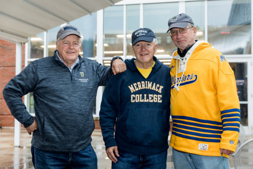 Jack Pasini '73, left, with friends celebrating outside the Sakowich Campus Center. Photo by...