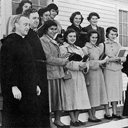 Old photo of women singing with priests.