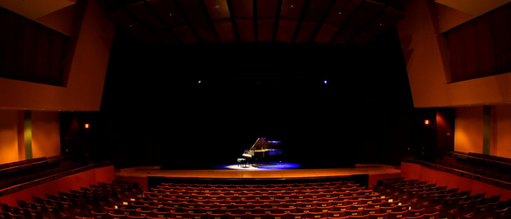 A piano sits center stage in the Rogers Center for the Arts.
