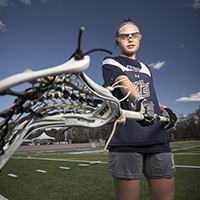 women's lacrosse player holding stick.